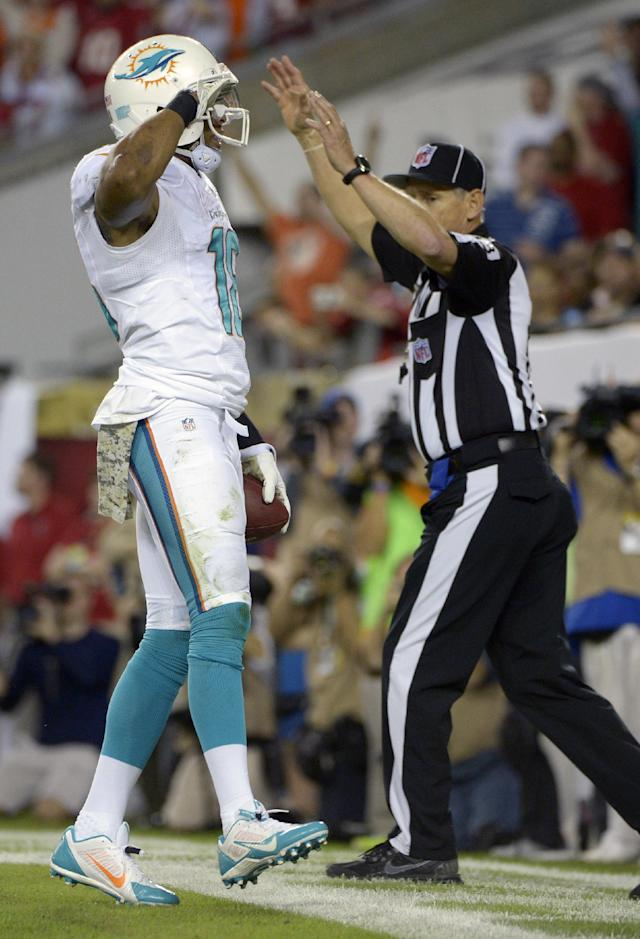 Miami Dolphins wide receiver Rishard Matthews, left, salutes the fans after scoring a touchdown on a 6-yard pass play against the Tampa Bay Buccaneers during the first half of an NFL football game in Tampa, Fla., Monday, Nov. 11, 2013.(AP Photo/Phelan M. Ebenhack)