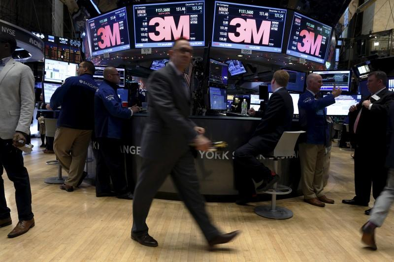 Traders work around the post where 3M is traded on the floor of the New York Stock Exchange