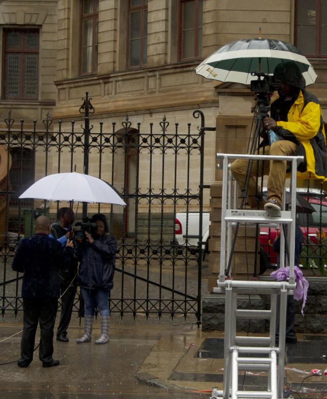 Television journalists await the arrival of Oscar Pistorius outside the high court in Pretoria, South Africa, Tuesday, March 4, 2014. Pistorius is charged with murder for the shooting death of his girlfriend, Reeva Steenkamp, on Valentines Day in 2013. (AP Photo/Themba Hadebe)