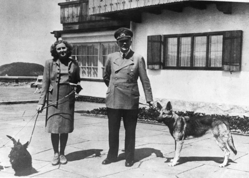 The German Chancellor Adolf Hitler and his mistress Eva Braun with their dogs at Bertesgaden, ca. 1935. (Photo by © Hulton-Deutsch Collection/CORBIS/Corbis via Getty Images)