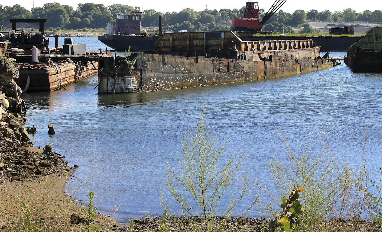 "In this Monday, Aug. 22, 2016, photo, rusting remnants of an old Russian submarine that once was used as a floating museum until it sank in 2007, remains in the Providence river in Providence, R.I. The state wants it gone. Known as Juliett 484, the sub served as a set for the 2002 Harrison Ford movie ""K-19: The Widowmaker."" It was moved in 2009 to a scrap metal facility, but the company stopped working on it in 2014. (AP Photo/Jennifer McDermott)"