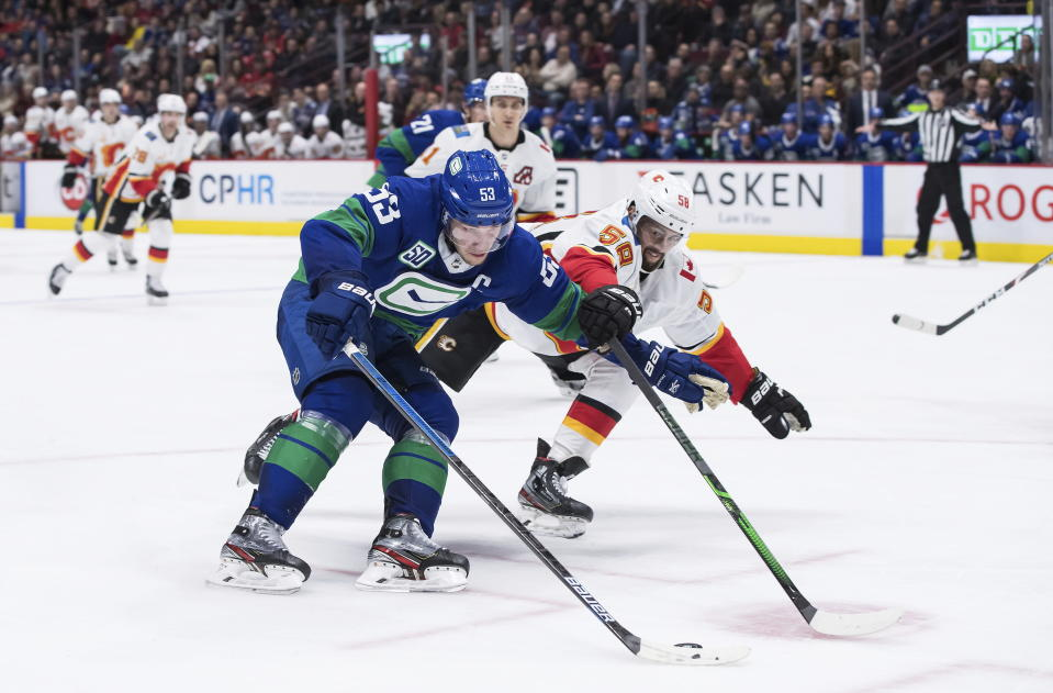 Vancouver Canucks' Bo Horvat (53) skates with the puck past Calgary Flames' Oliver Kylington (58), of Sweden, during the second period of an NHL hockey game Saturday, Feb. 8, 2020, in Vancouver, British Columbia. (Darryl Dyck/The Canadian Press via AP)