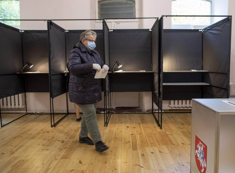 A woman, wearing a face mask to protect against coronavirus walks to cast her ballot at a polling station during parliamentary elections in Vilnius, Lithuania, Sunday, Oct.11, 2020. Polls opened Sunday for the first round of national election in Lithuania, where voters will renew the 141-seat parliament and the ruling four-party coalition is widely expected to face a stiff challenge from the opposition to remain in office. (AP Photo/Mindaugas Kulbis)