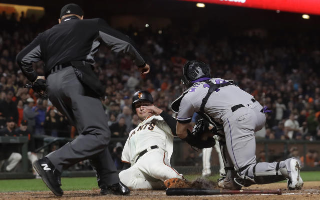Umpire Vic Carapazza, left, watches as Colorado Rockies catcher Tony Wolters, right, tags out San Francisco Giants' Joe Panik at home during the seventh inning of a baseball game in San Francisco, Monday, June 24, 2019. (AP Photo/Jeff Chiu)