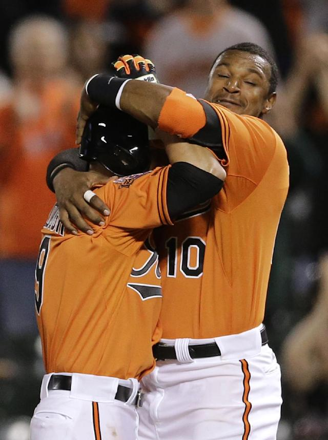 Baltimore Orioles' David Lough, left, celebrates with Adam Jones after hitting a game-winning single in the 12th inning of a baseball game against the Toronto Blue Jays, Saturday, April 12, 2014, in Baltimore. Stephen Lombardozzi scored on the play, and Baltimore won 2-1. (AP Photo/Patrick Semansky)