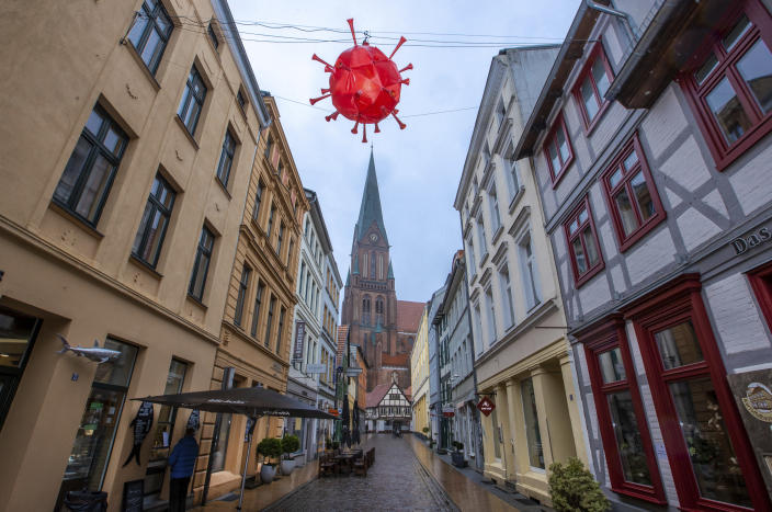 A homemade, luminous representation of the coronavirus hangs above a shopping street in front of the tower of Schwerin Cathedral during the lockdown in Schwerin, Germany, Tuesday, Jan. 5, 2021. A local fishmonger in the almost deserted street built and hung the lantern in the image of the virus. The German Chancellor and the Minister Presidents of the federal states discuss an extension of the lockdown to contain the corona pandemic. (Jens Buettner/dpa via AP)