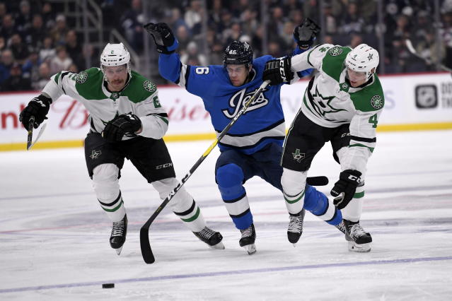 Winnipeg Jets' Joona Luoto (46) is checked by Dallas Stars' Jamie Oleksiak (2) and Miro Heiskanen (4) during second-period NHL hockey game action in Winnipeg, Manitoba, Sunday, Nov. 10, 2019. (Fred Greenslade/The Canadian Press via AP)