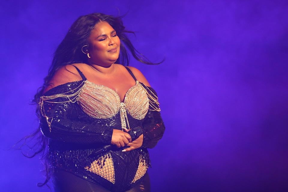 Lizzo wearing a black and silver outfit while performing on stage.