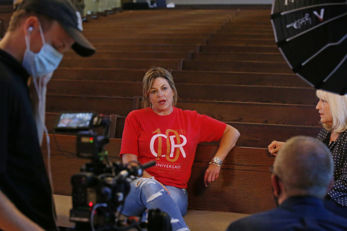 Teresa Stanfield, seated at center, the Oklahoma field director with Virginia-based Prison Fellowship, and Teresa Peden, seated right, pastor of recovery ministry at Crossing Community Church, talk with Drew Darby, left, and Topher Hall, foreground right, during a videotaping, Tuesday, Aug. 11, 2020, in Oklahoma City. Normally, Stanfield is behind bars, talking with inmates about how she changed the course of her troubled life. The coronavirus has forced her out of prisons. For the time being, Stanfield is videotaping her message. (AP Photo/Sue Ogrocki)