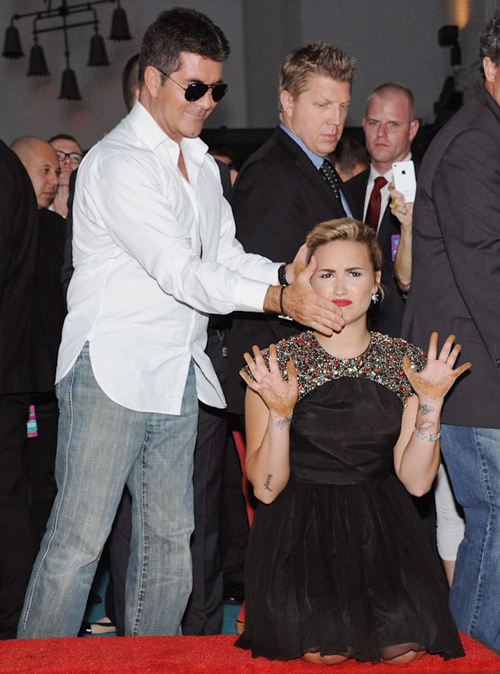 Simon Cowell smears his hand on Demi Lovato's face at the 'The X Factor' Season 2 Premiere Party at Grauman's Chinese Theatre on September 11, 2012 in Hollywood, California.