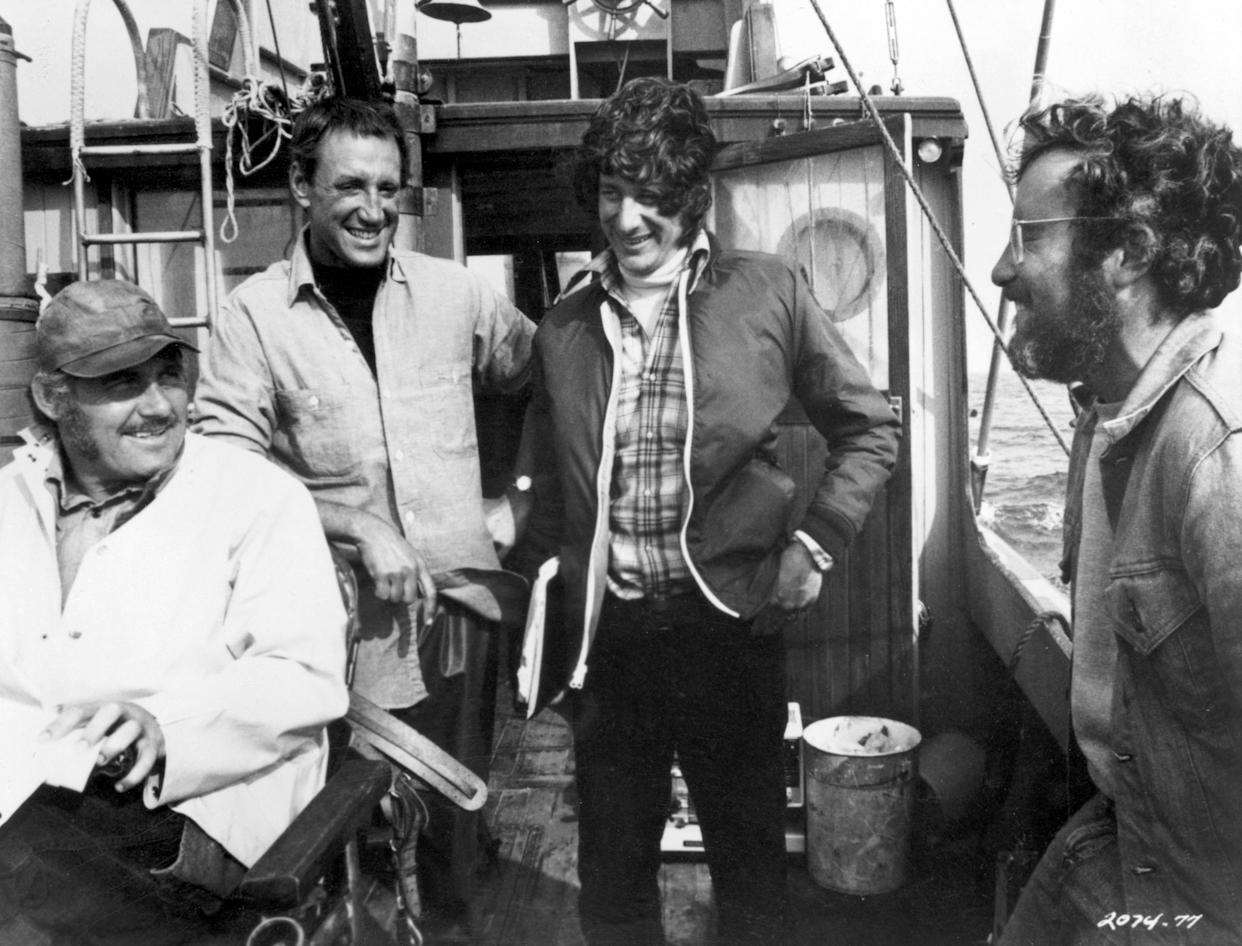1975, British actor Robert Shaw, American actor Roy Scheider, American director Steven Spielberg, and American actor Richard Dreyfuss laugh together on a boat during the filming of Spielberg's 'Jaws'. (Photo by Universal Studios/Getty Images)
