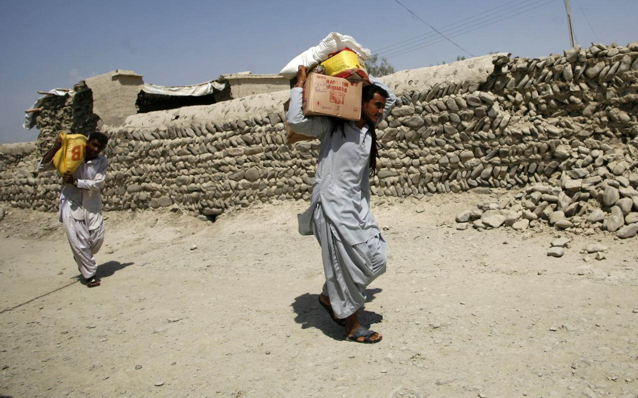 Survivors of an earthquake carry relief goods that were collected from a distribution point in the town of Awaran