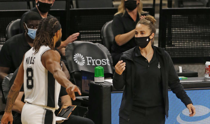 Becky Hammon, wearing a mask, talks to Patty Mills during a break in play.