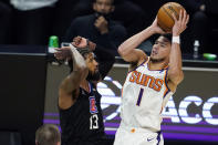 Phoenix Suns guard Devin Booker (1) shoots over Los Angeles Clippers guard Paul George (13) during the first half of an NBA basketball game Thursday, April 8, 2021, in Los Angeles. (AP Photo/Marcio Jose Sanchez)