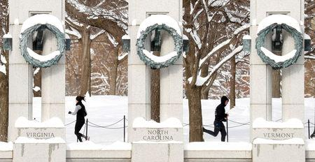 Joggers pass one another, following the weekend's snowstorm, at the World War II Memorial in Washington, U.S., January 14, 2019. REUTERS/Kevin Lamarque
