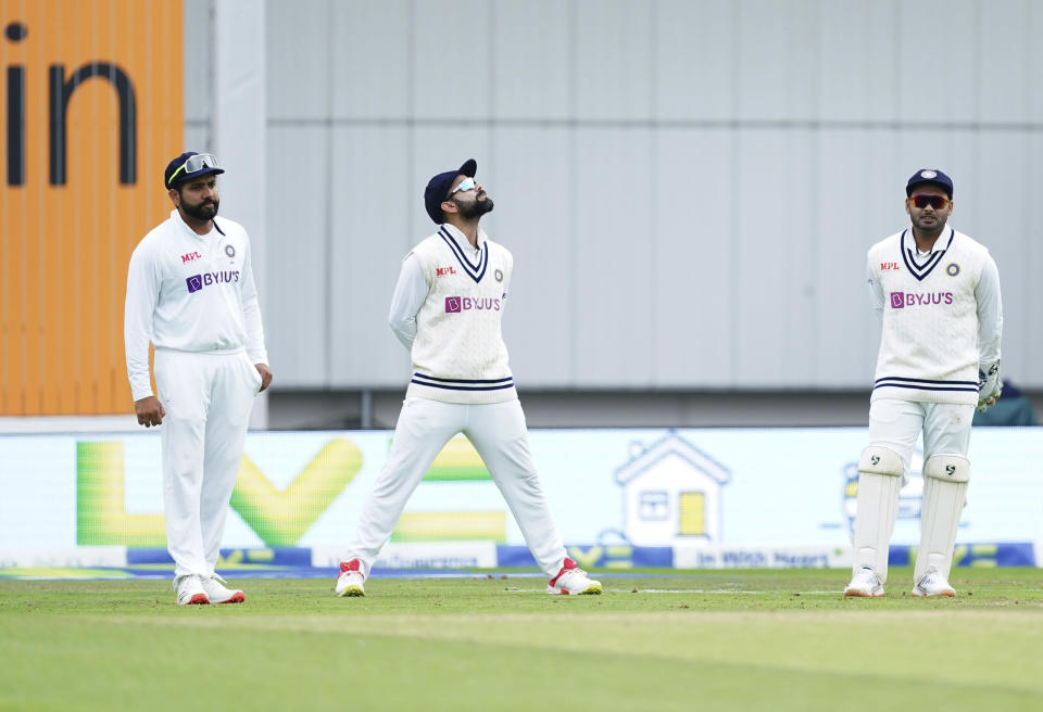 India's captain Virat Kohli, center, and teammates Rohit Sharma, left, and wicketkeeper Rishabh Pant stand at their fielding positions during the first day of third test cricket match between England and India, at Headingley cricket ground in Leeds, England, Wednesday, Aug. 25, 2021. (AP Photo/Jon Super)