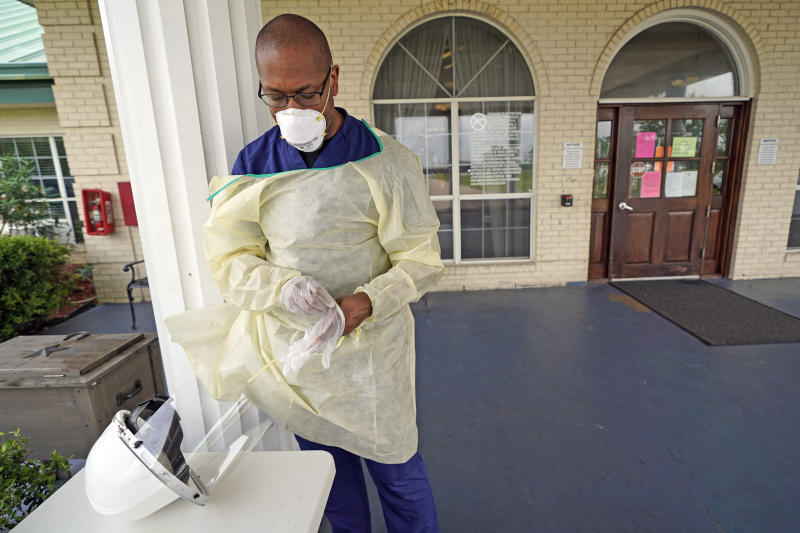 Dr. Robin Armstrong puts on his gloves while demonstrating his full personal protective equipment outside the entrance to The Resort at Texas City nursing home, where he is the medical director, Tuesday, April 7, 2020, in Texas City, Texas. Armstrong is treating nearly 30 residents of the nursing home with the anti-malaria drug hydroxychloroquine, which is unproven against COVID-19 even as President Donald Trump heavily promotes it as a possible treatment. Armstrong said Trump's championing of the drug is giving doctors more access to try it on coronavirus patients. More than 80 residents and workers have tested positive for coronavirus at the nursing home. (AP Photo/David J. Phillip)