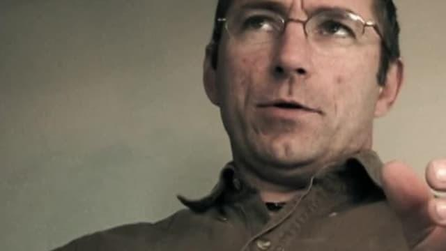 Man with glasses speaks to camera