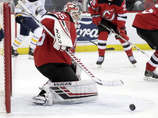 New Jersey Devils goaltender Cory Schneider eyes the puck during the third period of an NHL hockey game against the Buffalo Sabres, Monday, March 25, 2019, in Newark, N.J. The Devils won 3-1. (AP Photo/Julio Cortez)