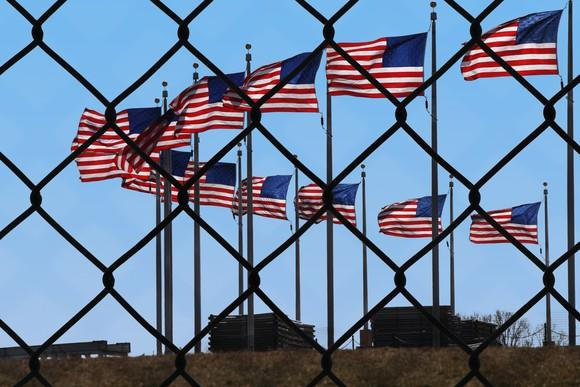View through a chain-link fence at U.S. flags