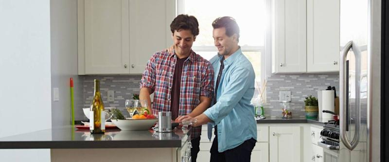 Male couple in the kitchen preparing a meal, looking down