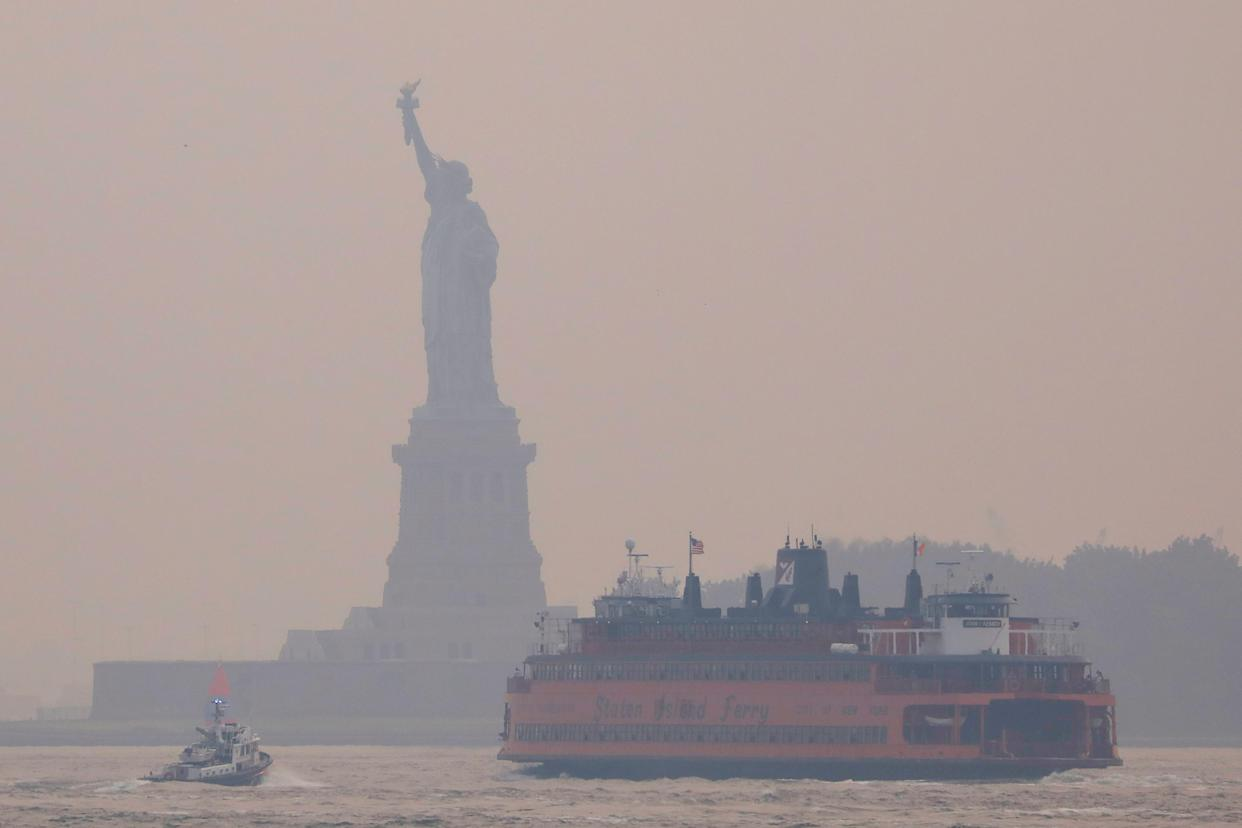 Boats in front of the Statue of Liberty, which is seen through a cover of wildfire smoke