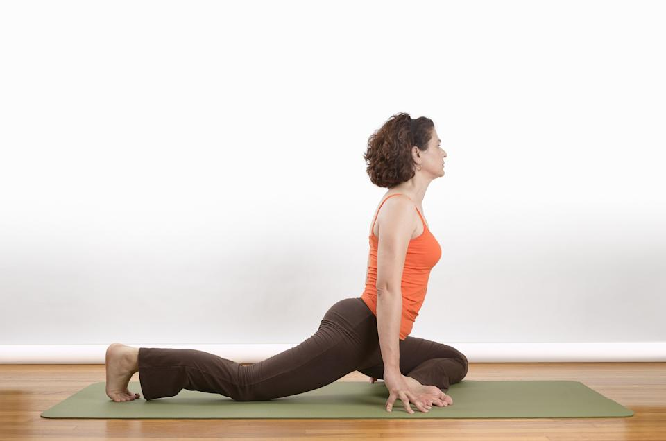 """The hips can get tight from long hours of sitting. To improve flexibility and range of motion in the hips, and open up the chest and shoulders, try a half pigeon pose. Start on your hands and knees in a tabletop position, sliding the right knee forward and left leg back, as pictured above, trying to bend the front leg at a 90-degree angle. Sit up tall, and on the exhale, hinge the chest forward and bring the arms out in front of you to feel a deep stretch.  """"A half pigeon is great for opening up the hips,"""" Bielkus says.  If you're particularly tight in the hips, try rolling up a blanket under the hips and sitting upright, and then gently hinging forward."""