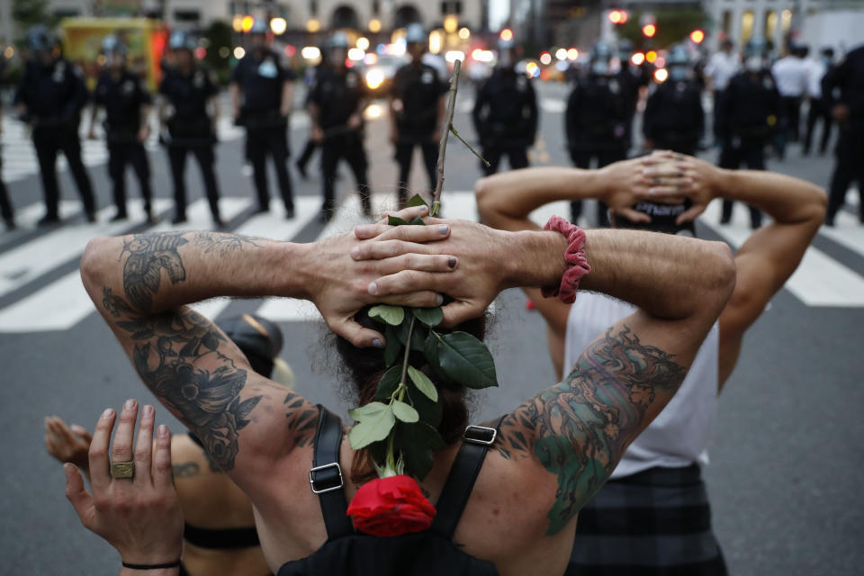 Protesters kneel in front of New York City Police Department officers before being arrested for violating curfew beside the iconic Plaza Hotel on 59th Street, Wednesday, June 3, 2020, in New York. (AP Photo/John Minchillo)