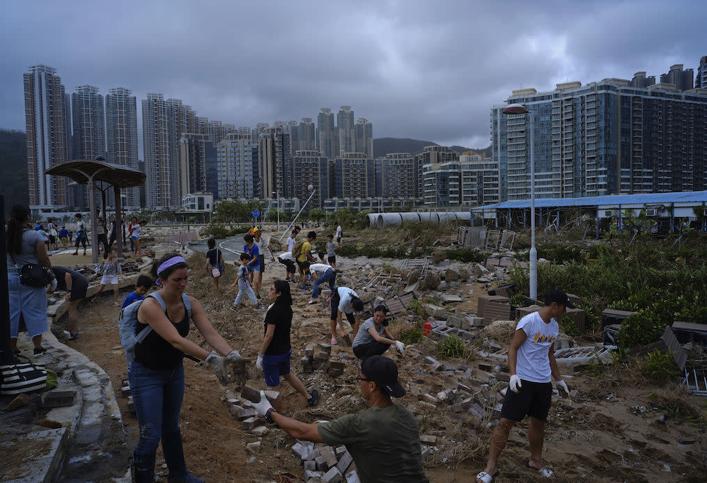 <p>People clean debris from Typhoon Mangkhut on the waterfront in Hong Kong (Picture: AP) </p>