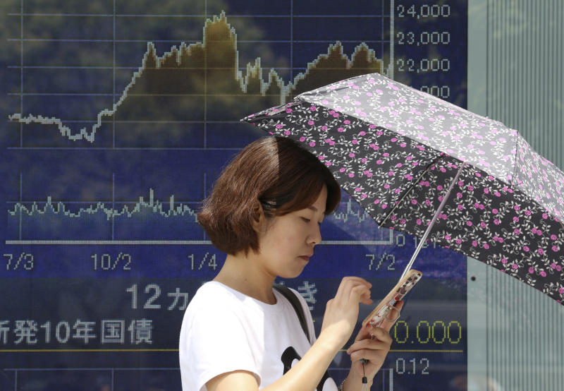 In this Wednesday, July 11, 2018, photo, a woman stands in front of an electronic stock board of a securities firm in Tokyo. Asian stock markets rose Thursday, July 12, 2018, following Wall Street's decline amid U.S.-Chinese trade tensions and oil prices recovered some of the previous day's steep losses. (AP Photo/Koji Sasahara)