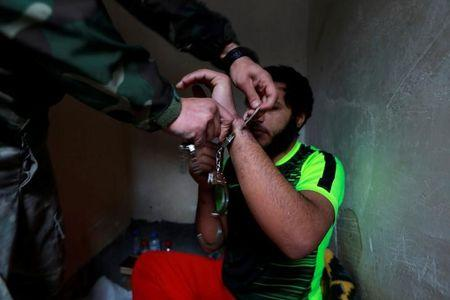 An Islamic State member has his cuff removed by a counter-terrorism agent inside his prison cell  in Sulaimaniya