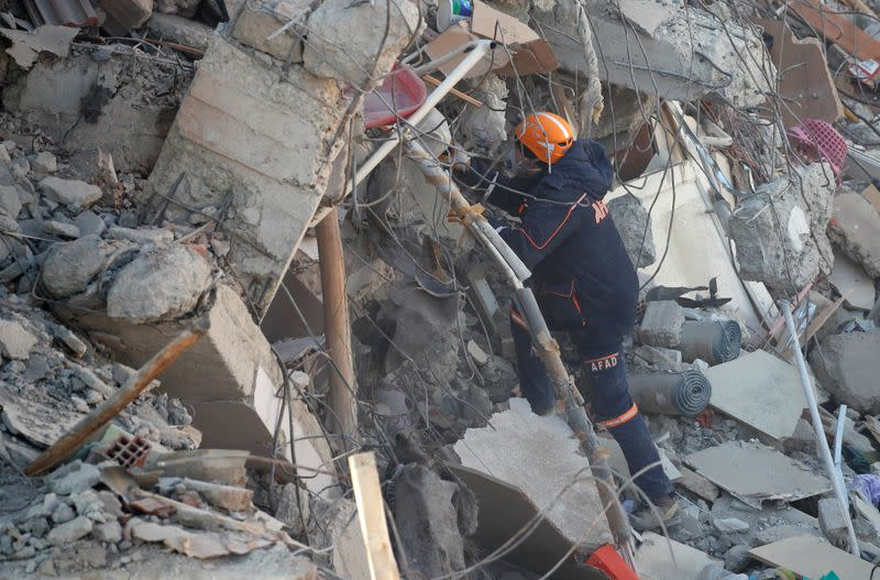 A rescue worker searches at the site of a collapsed building, after an earthquake in Elazig