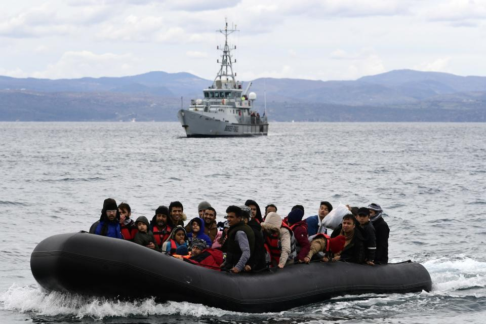 FILE - In this Friday Feb. 28, 2020 file photo, refugees and migrants arrive in a dinghy accompanied by Frontex vessels at the village of Skala Sikaminias, on the Greek island of Lesbos, after crossing the Aegean sea from Turkey. Human rights lawyers said on Tuesday, May 25, 2021, that they have launched legal action against the European Union's border and coast guard agency at the bloc's top court, accusing Frontex of violating the rights of people trying to seek asylum and other breaches of international law. (AP Photo/Michael Varaklas, File)