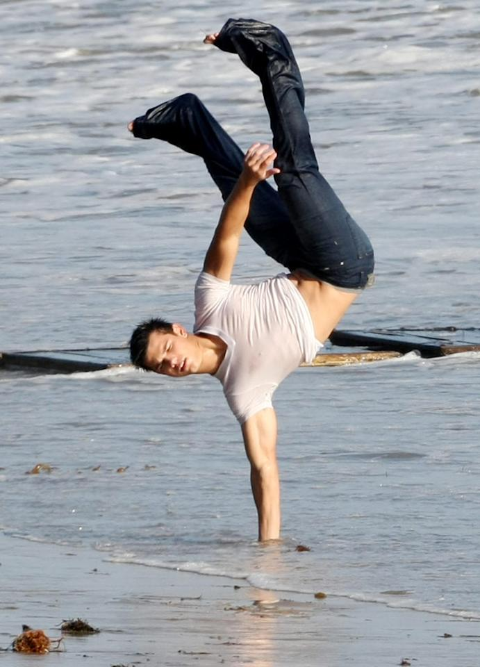 "Look familiar? Taylor performed gymnastics, just as he did as a kid on the red carpet, during a photo shoot for his December 2009 cover of <i>Rolling Stone</i> magazine. Johnstone/Raishbrook/<a href=""http://www.splashnewsonline.com"" target=""new"">Splash News</a> - October 8, 2009"