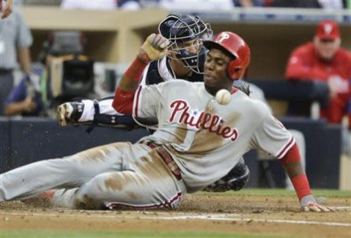 San Diego Padres catcher Yasmani Grandal reaches for the throw as it hits Philadelphia Phillies' John Mayberry Jr. while scoring in the second inning of a baseball game in San Diego, Monday, June 24, 2013. (AP Photo/Lenny Ignelzi)