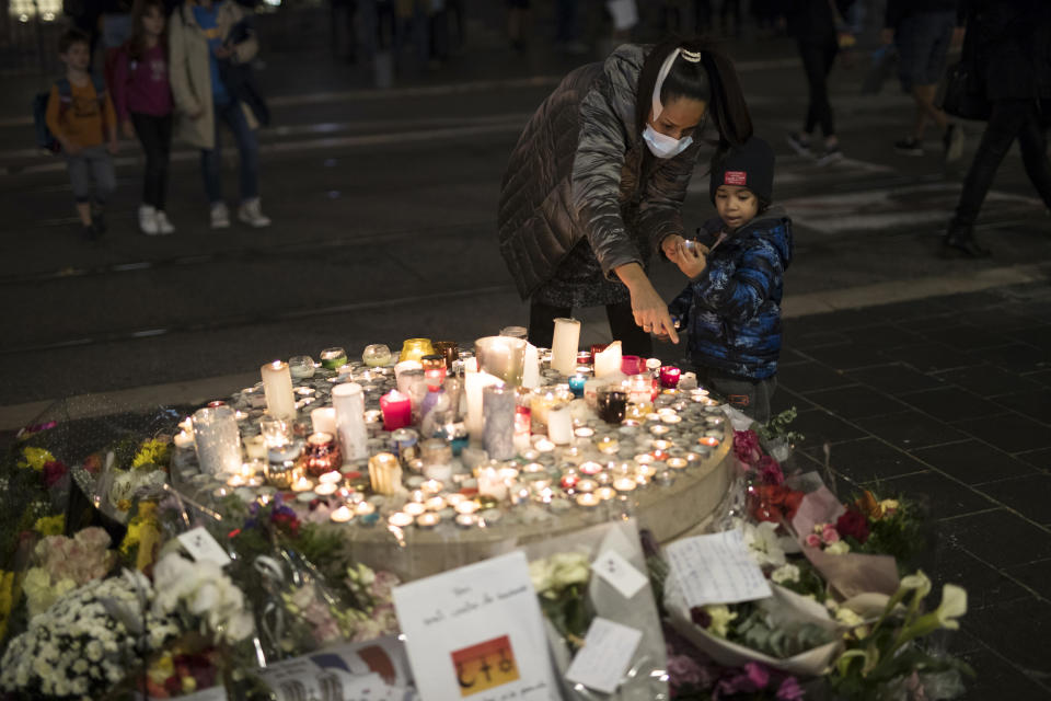 A family lights a candle in front of the Notre Dame church in Nice, France, Friday, Oct. 30, 2020. A new suspect is in custody in the investigation into a gruesome attack by a Tunisian man who killed three people in a French church. France heightened its security alert amid religious and geopolitical tensions around cartoons mocking the Muslim prophet. (AP Photo/Daniel Cole)
