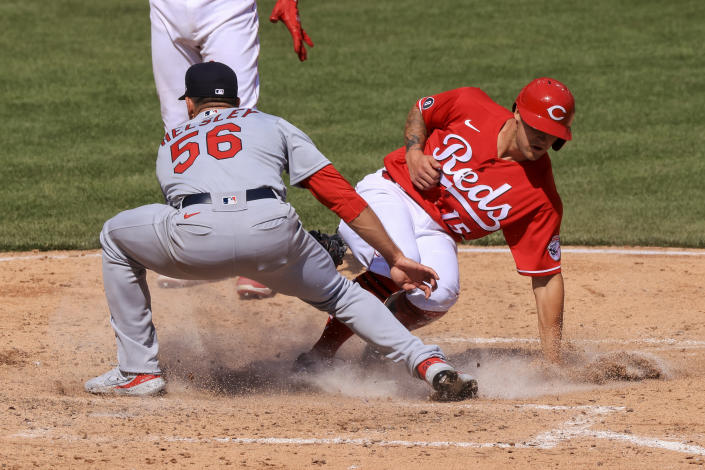 Cincinnati Reds' Nick Senzel, right, scores a run ahead of the tag from St. Louis Cardinals' Ryan Helsley during the sixth inning of a baseball game in Cincinnati, Sunday, April 4, 2021. (AP Photo/Aaron Doster)