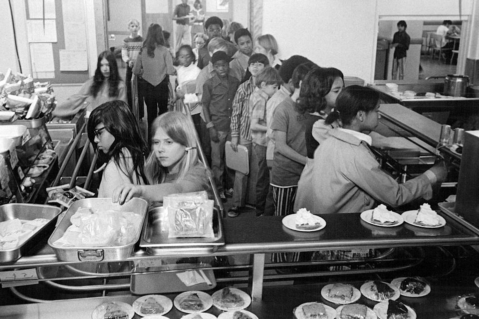 """<p>Kids wait on long lines to grab their lunch from the cafeteria. </p><p><strong>RELATED:</strong> <a href=""""https://www.goodhousekeeping.com/life/parenting/g27532924/bento-box-lunches/"""" rel=""""nofollow noopener"""" target=""""_blank"""" data-ylk=""""slk:These Creative Bento Box Lunches Will Make Your Kid the Envy of the Cafeteria"""" class=""""link rapid-noclick-resp"""">These Creative Bento Box Lunches Will Make Your Kid the Envy of the Cafeteria</a></p>"""