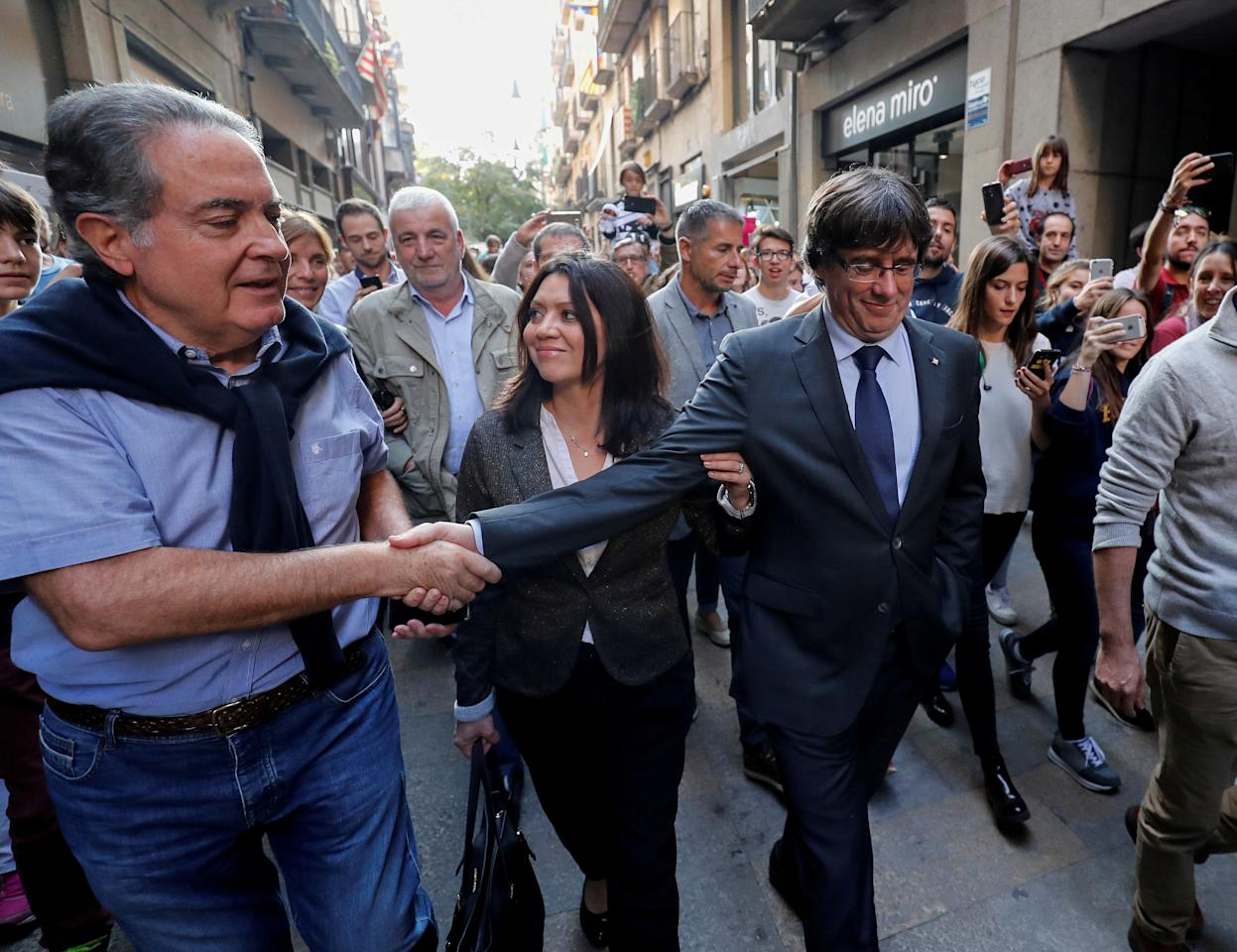 <p>Sacked Catalan President Carles Puigdemont (R) walks with his wife Marcela Topor as he greets a supporter after leaving a restaurant the day after the Catalan regional parliament declared independence from Spain in Girona, Spain, Oct. 28, 2017. (Photo: Rafael Marchante/Reuters) </p>