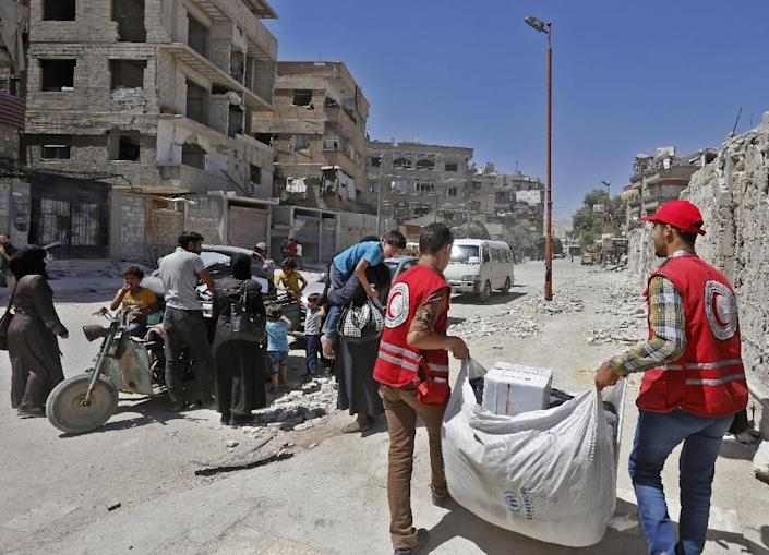 Members of the Syrian Arab Red Crescent distribute humanitarian aid to residents of the town of Douma as tens ouf thousands of Syrians in areas recaptured by government troops this year remain starved of humanitarian aid (AFP Photo/LOUAI BESHARA)