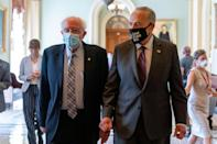 Sen. Bernie Sanders, I-Vt., left, and Senate Majority Leader Chuck Schumer, D-N.Y., right, walk out of a budget resolution meeting at the Capitol on Monday.