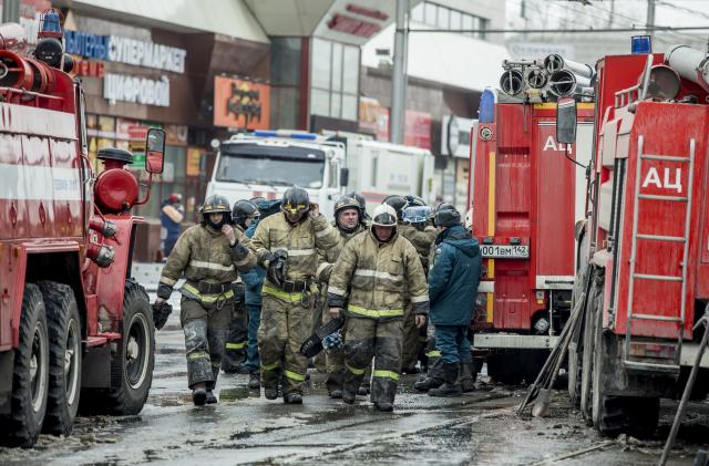 <p>A group of firefighters walk near the scene of the multistory shopping center after a fire in the Siberian city of Kemerovo, about 3,000 kilometers (1,900 miles) east of Moscow, March 26, 2018. Russian officials say a fire at the shopping mall killed over 50 people. The Ekho Mosvky radio station quoted witnesses who said that the fire alarm did not go off and that the staff in the mall in Kemerovo did not organize the evacuation. (AP Photo) </p>