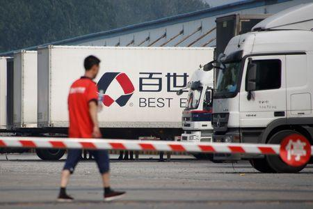 A man walks in the compound of a distribution hub of the Chinese logistics company Best Inc in Beijing