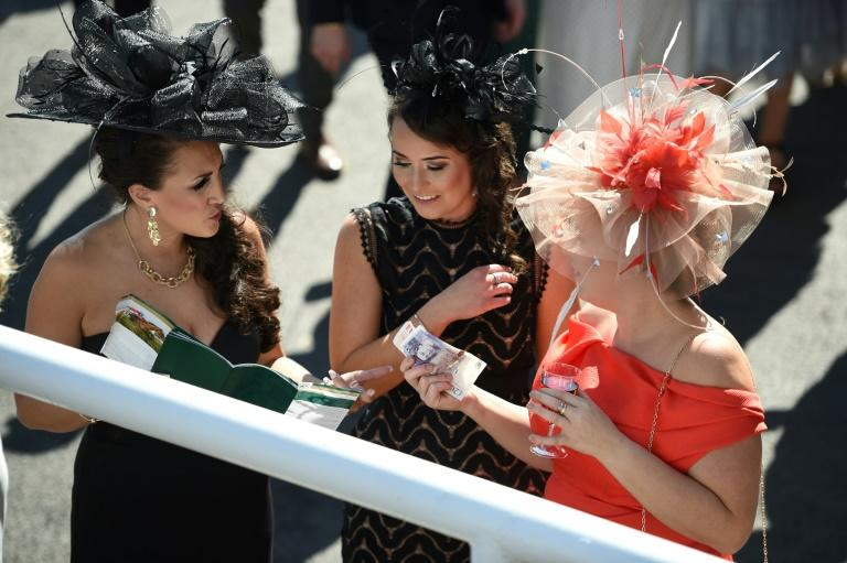 Racegoers study the form before placing bets on the first race of the final day of the Grand National Festival meeting at Aintree Racecourse in Liverpool, northwest England on April 8, 2017