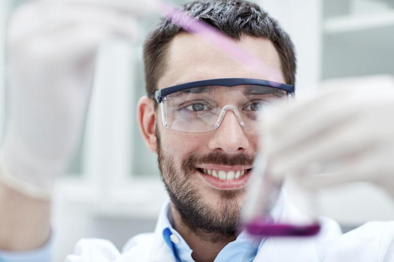 Smiling person holding a pipette and a flask.
