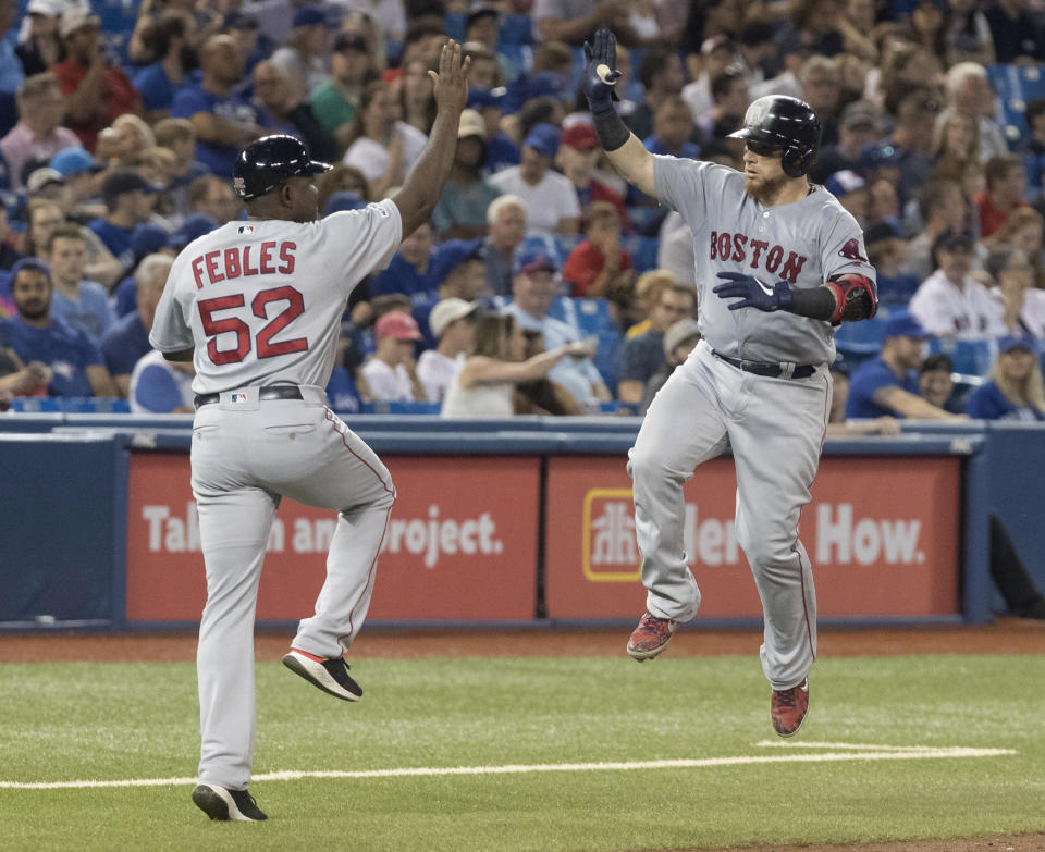 Boston Red Sox's Christian Vasquez gets a high-five from third base coach Carlos Febles after hitting a solo home run against the Toronto Blue Jays during the seventh inning of a baseball game Tuesday, July 2, 2019, in Toronto. (Fred Thornhill/The Canadian Press via AP)