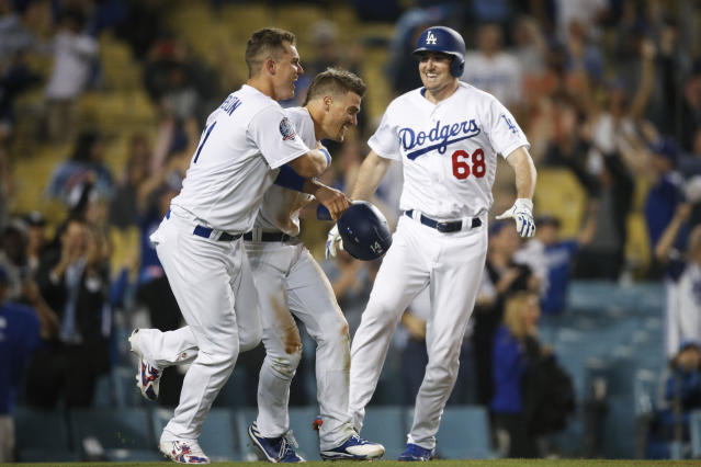 Los Angeles Dodgers' Enrique Hernandez, center, is congratulated by Joc Pederson, left, and Ross Stripling after scoring a game-winning run on a throwing error by Texas Rangers relief pitcher Matt Bush during the 11th inning of a baseball game, Wednesday, June 13, 2018, in Los Angeles. The Dodgers won 3-2. (AP Photo/Jae C. Hong)