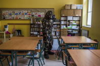 A Hungarian soldier wearing a hazmat suit disinfects a classroom of a combined kindergarten and elementary school in an effort to curb the spread of the pandemic of the new coronavirus in Budapest, Hungary, Wednesday, March 17, 2021. (Zoltan Balogh/MTI via AP)