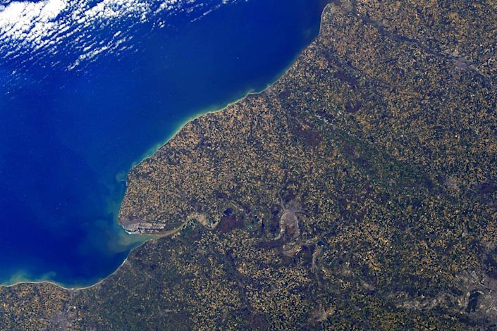 normandy france coast purple yellow green speckled land against deep blue ocean