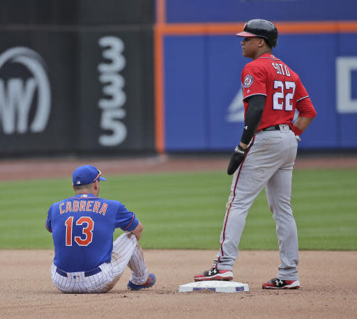 New York Mets second baseman Asdrubal Cabrera, left, sits on the ground after failing to tag Washington Nationals' Juan Soto, right, during the seventh inning of a baseball game at Citi Field, Sunday, July 15, 2018, in New York. (AP Photo/Seth Wenig)